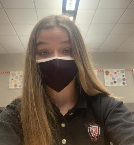 Freshmen Averi Langin poses for a masked-up selfie during the school day.