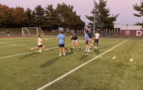 Freshmen boys play a competitive game of Spikeball