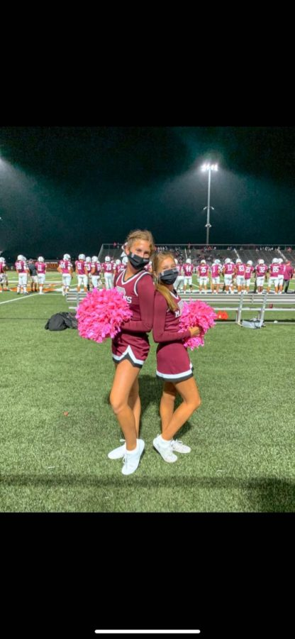 Harshbarger (10) and Nicole Pedersen (10) cheering on the sidelines for football while staying safe.