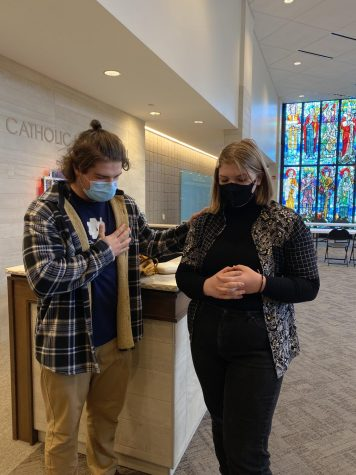 Stanfel praying upon senior, Ellie Coleman in the Dowling Narthex